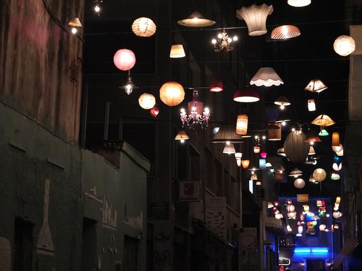 Bella instalación de luces ilumina con diferentes pantallas una antigua calle de Grecia